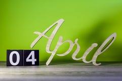 April 4th Dag 4 av månaden, kalender på trätabellen och gräsplanbakgrund Vårtid, tömmer utrymme för text Royaltyfri Bild
