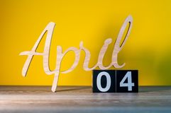 April 4th Dag 4 av månaden, kalender på trätabellen och gulingbakgrund Fjädra den tid… ron lämnar, naturlig bakgrund Royaltyfria Bilder