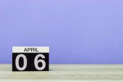 April 6th Dag 6 av månaden, kalender på trätabellen och lilabakgrund Vårtid, tömmer utrymme för text Arkivfoto