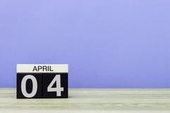 April 4th Dag 4 av månaden, kalender på trätabellen och lilabakgrund Vårtid, tömmer utrymme för text Royaltyfri Fotografi