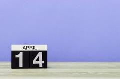 April 14th Dag 14 av månaden, kalender på trätabellen och lilabakgrund Vårtid, tömmer utrymme för text Arkivfoto