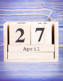 April 27th. Date of 27 April on wooden cube calendar. Purple board as background Stock Photo