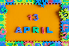 April 13th. Day 13 of month, daily calendar of child toy puzzle at orange background. Spring time theme Royalty Free Stock Photos