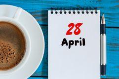 April 28th. Day 28 of month, calendar with morning coffee cup, at workplace. Spring time, Top view.  Royalty Free Stock Images