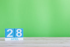 April 28th. Day 28 of month, calendar on wooden table and green background. Spring time, empty space for text Royalty Free Stock Photo