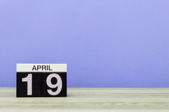 April 19th. Day 19 of month, calendar on wooden table and purple background. Spring time, empty space for text Stock Images