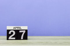 April 27th. Day 27 of month, calendar on wooden table and purple background. Spring time, empty space for text Royalty Free Stock Photography