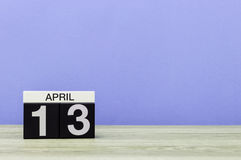 April 13th. Day 13 of month, calendar on wooden table and purple background. Spring time, empty space for text Royalty Free Stock Photo