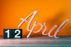 April 12th. Day 12 of month, daily wooden calendar on table with orange background. Spring time concept Royalty Free Stock Photo
