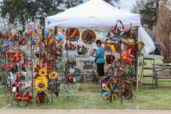 April 13 2018 Tulsa USA Tent booth at spring garden fair with all kinds of brightly colored yard ornaments on display and woman. Shopping royalty free stock photo