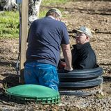 APRIL 27, 2017 - Two men repair septic tank in Ridgway Colorado - appear to be in a hole in the. Men, repair stock photography