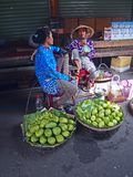 4 April, 2015 - Vietnamese women sitting in a market in Nha Trang Cho Dam Market. Vietnamese women selling green mangoes in baskets in a market in Nha Trang Cho Royalty Free Stock Image