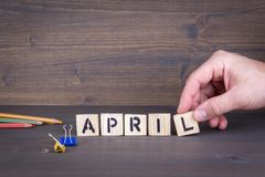 April. Wooden letters on the office desk, informative and communication background royalty free stock image
