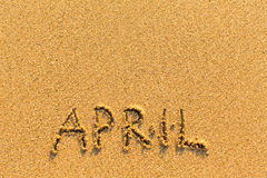 April - word inscription on the gold sand beach. Stock Image