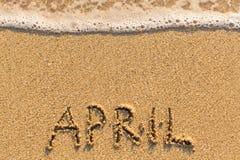 April - Wort gezeichnet auf den Sandstrand mit der weichen Welle Lizenzfreies Stockbild