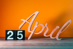 25 aprile Giorno 25 del mese, calendario di legno quotidiano sulla tavola con fondo arancio Concetto di tempo di primavera Immagini Stock