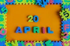 20 aprile Giorno 20 del mese, calendario quotidiano del puzzle del giocattolo del bambino su fondo arancio Tema di tempo di prima Immagini Stock