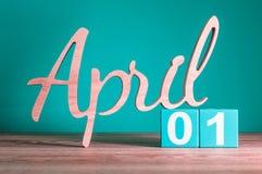 1° aprile giorno 1 del mese, calendario quotidiano sulla tavola di legno con fondo verde Tema di tempo di primavera Fotografia Stock