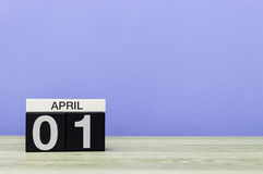 1° aprile giorno 1 del mese, calendario sulla tavola di legno e fondo porpora Tempo di primavera, spazio vuoto per testo Fotografia Stock Libera da Diritti