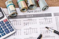 15 aprile, giorno di imposta sul calendario con la penna di indicatore rossa con la banconota del dollaro Fotografie Stock
