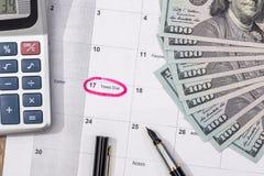 15 aprile, giorno di imposta sul calendario con la penna di indicatore rossa con la banconota del dollaro Fotografia Stock