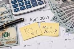 15 aprile, giorno di imposta sul calendario con la penna di indicatore rossa con la banconota del dollaro, penna Fotografie Stock