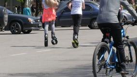 21 aprile 2018 - Kamenskoye, Ucraina: Le ragazze stanno correndo lungo la via in saltatori, scarpe speciali sulle molle, ciclista stock footage
