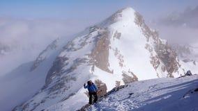 Aprobaty od męskiej backcountry narciarki wycieczkuje wysoki wysokogórski szczyt w Szwajcaria wzdłuż rockowej i śnieżnej grani w  obraz stock