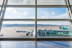 Airplane at parking position of airport waiting for next flight. The apron from passenger terminal stock image