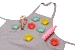 Apron with rolling pin, whisk, colorful muffin cups Stock Image