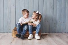 Apronte ao curso grande Livro interessante feliz da leitura da menina e do menino que leva uma pasta e um sorriso grandes Curso imagens de stock royalty free