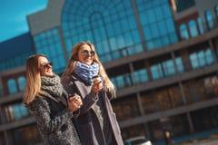 Apronte comprando! Retrato de duas mulheres bonitas nos revestimentos e nos óculos de sol que bebem o café ao andar exterior Imagem de Stock Royalty Free