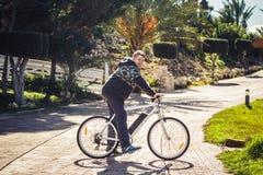 Apronte para montar Homem novo considerável na bicicleta que olha a câmera e que sorri ao estar fora Imagens de Stock Royalty Free