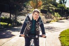 Apronte para montar Homem novo considerável na bicicleta que olha a câmera e que sorri ao estar fora Fotos de Stock