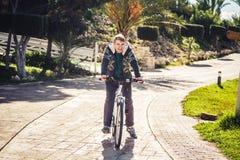 Apronte para montar Homem novo considerável na bicicleta que olha a câmera e que sorri ao estar fora Imagem de Stock Royalty Free