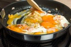 Apronte para o café da manhã: cozinhando ovos mexidos em uma cozinha moderna Imagens de Stock