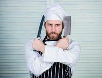 Apronte para trabalhar homem seguro na faca da posse do avental e do chapéu amores farpados do homem que comem o alimento cozinhe imagens de stock