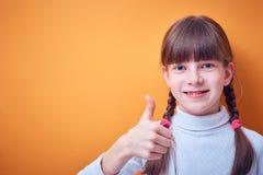 A aprovação e o acordo, menina adolescente caucasiano mostram o polegar acima no fundo colorido, lugar para o texto imagem de stock