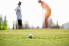 Aproximação da bola de golfe à posse no verde Acople o jogador de golfe que põe a bola de golfe no fundo Fotos de Stock Royalty Free