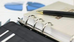 Aproximar-se perto acima do tiro da zorra, pena encontra-se em uma calculadora e em um caderno filme