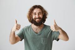 Apruebe su opción y apóyele Retrato del individuo hermoso amistoso con el pelo rizado que muestra los pulgares para arriba y la s imagen de archivo