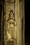 Apsara dancer bas-relief on ancient Angkor temple. Graceful female figure carved in a stone-bas relief on an ancient Angkorian temple in Angkor Wat, Cambodia. A Stock Image