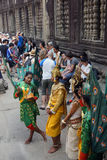 Apsara dancers wait by the sculptured wall Stock Photos