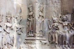 Apsara dansare stenar att snida, lite varstans på väggen på den Angkor waen Arkivfoton