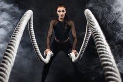 Aptidão com cordas da batalha Ajuste atrativo dos jovens e esporte-mulher tonificada Motivação do esporte e do exercício imagem de stock
