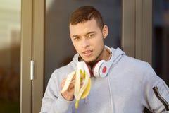 Aptidão de corrida do treinamento dos esportes do corredor do homem novo comer do fruto da banana fotografia de stock