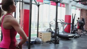Aptidão de Kettlebell, atleta fêmea novo que faz exercícios da força no gym vídeos de arquivo
