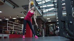Aptidão de Kettlebell, atleta fêmea novo que faz exercícios da força no gym filme