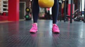 Aptidão de Kettlebell, atleta fêmea novo que faz exercícios da força no gym video estoque