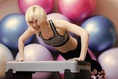 Aptidão diária Menina no treinamento do sportswear na plataforma da etapa no gym imagens de stock royalty free